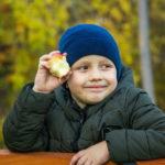 Мальчик с яблоком головы в парке осенью