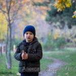 Мальчик потирает руки, стоя на тропинке в осеннем парке