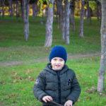 Мальчик с маленькой ветке дерева в руках в парке осенью
