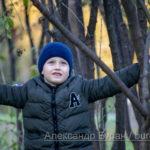 Мальчик среди ветвей молодых деревьев в парке осенью