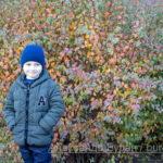 Мальчик улыбается, стоя возле кустов с яркими и необычными листьями осенью
