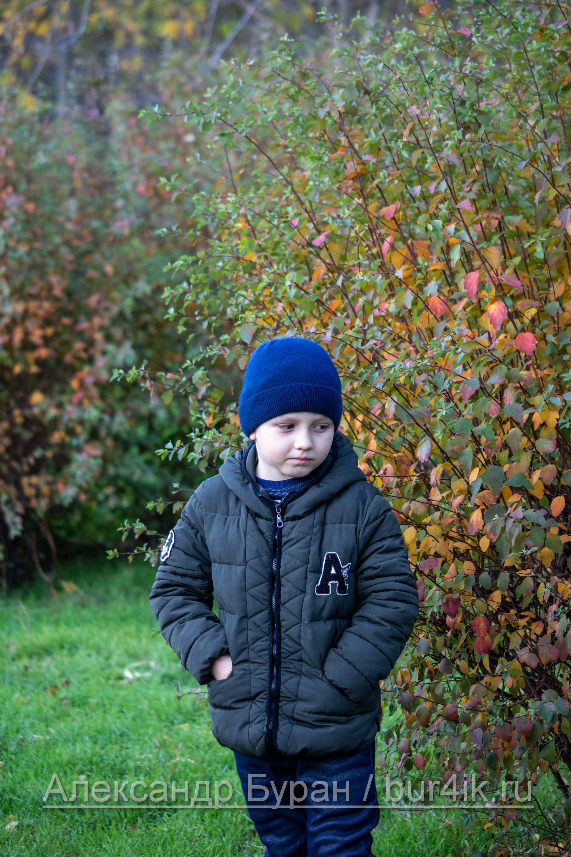 Мальчик смотрит вниз, проходя возле стены bushine в парке