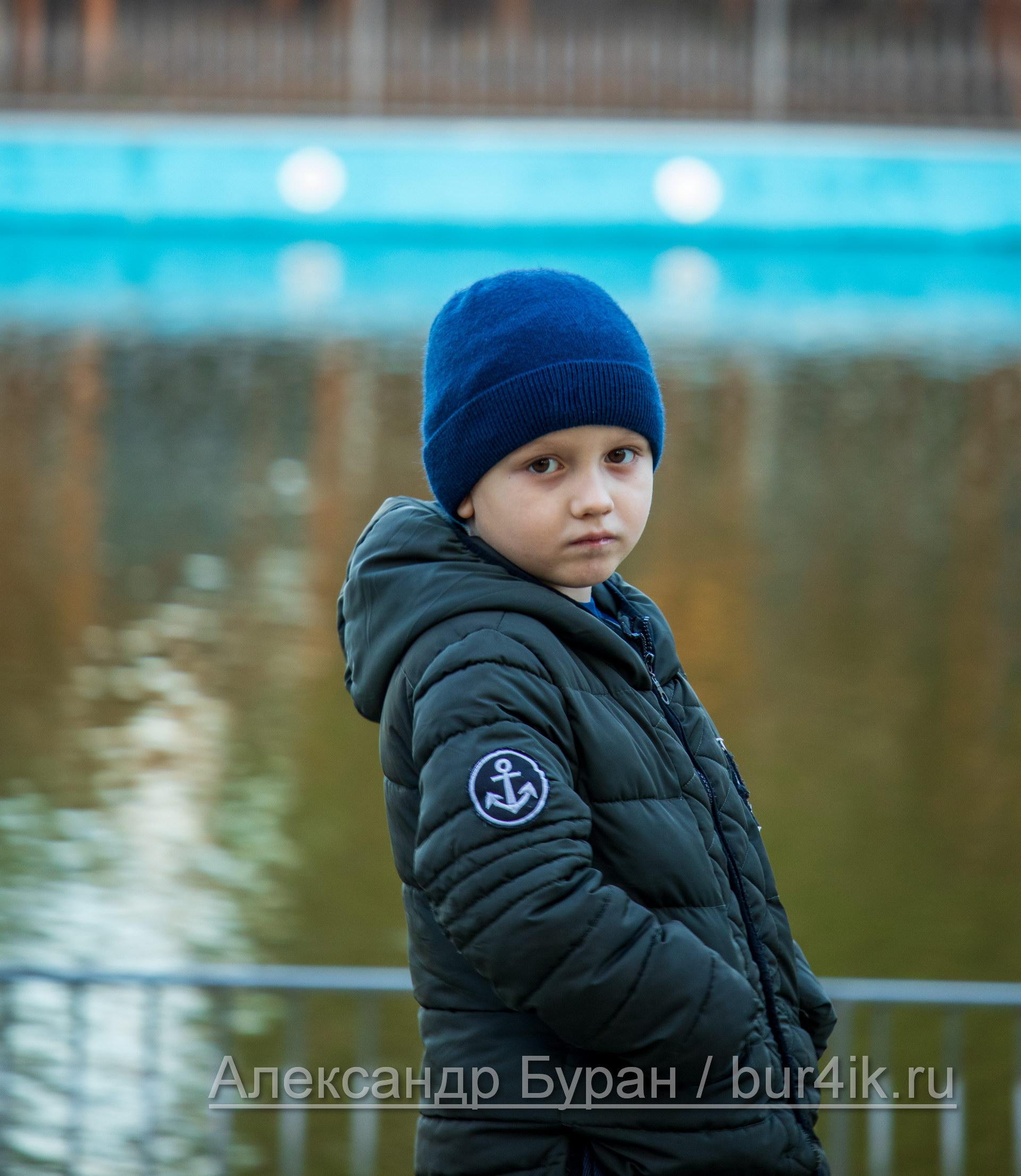 Мальчик в полоборота в парке у пруда