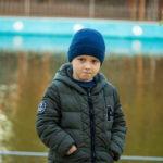 Мальчик закусывает губы на фоне воды в озере