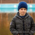 Портрет мальчика в синей кепке на берегу озера в парке