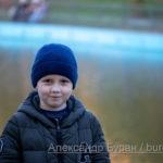 Шесть-летний мальчик осенью в парке около пруда с водой