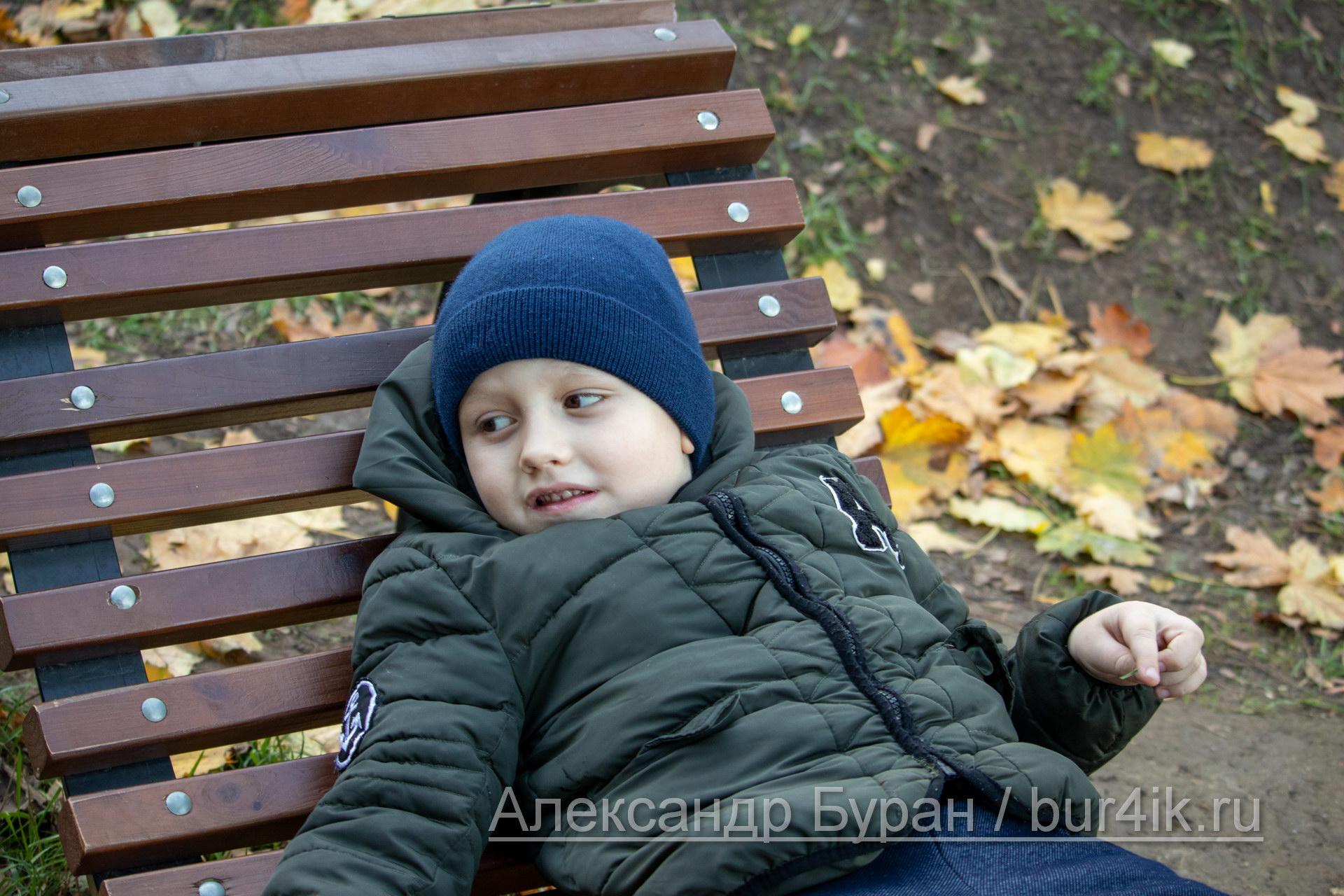Мальчик лежит на деревянном топает осенью в парке