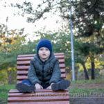 Мальчик сидит на деревянном топает осенью в парке