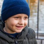 Улыбка мальчика в синей кепке на фоне озера