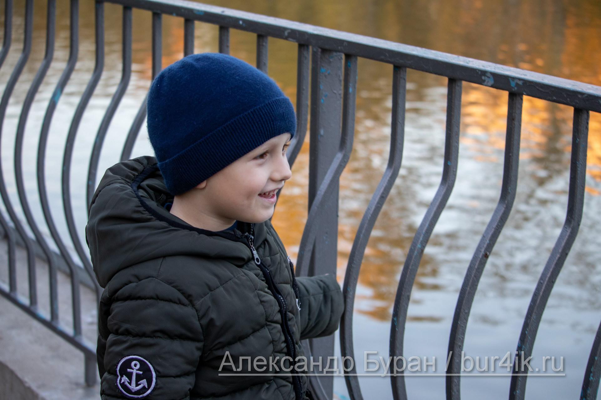 Мальчик стоит возле металлических перил, ограждающих озере в парке