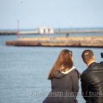Влюбленная парочка берет селфи, сидя на скамейке в порту, у воды - Украина, Одесса, 09,11,2019