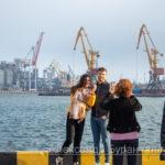 Молодая девушка и парень, которые фотографируют их родителей на прогулку в порту - Украина, Одесса, 09,11,2019