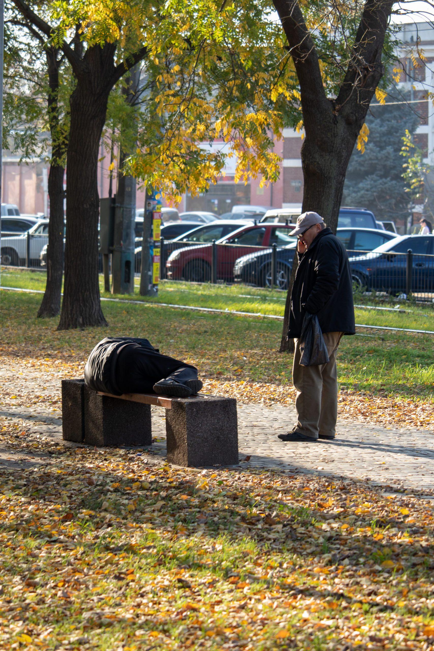 Бездомный пьяный мужчина спит на скамейке прямо на улице среди прохожих осенью – bur4ik.ru фото3