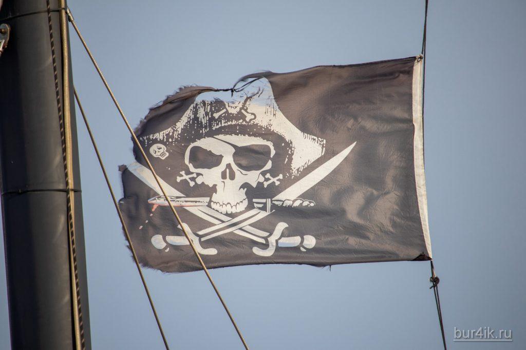 Черный пиратский флаг с черепом и саблями на мачте фрегата