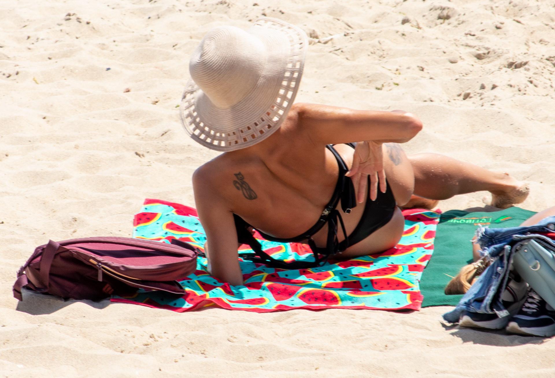 Женщина в шляпе загорает на море